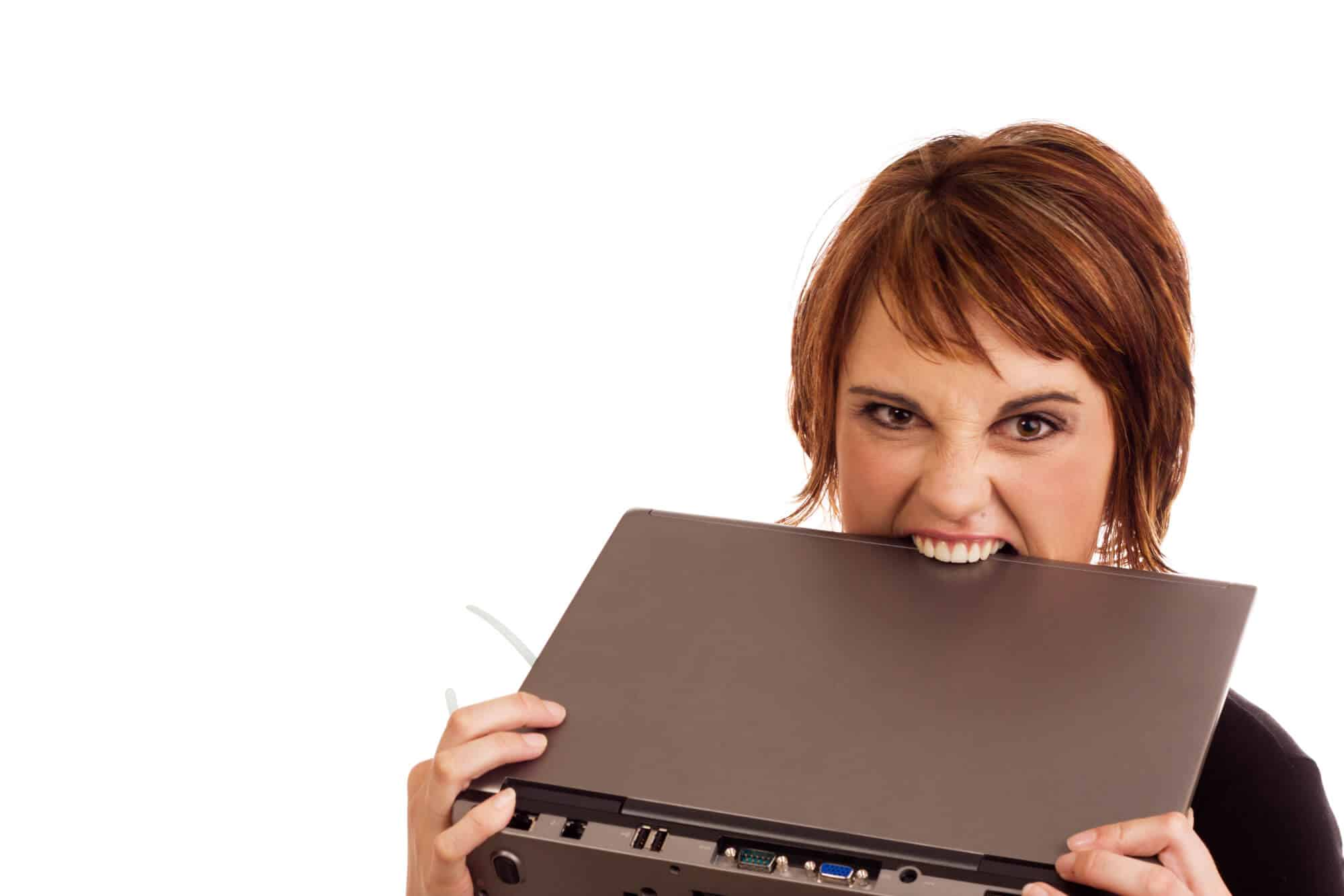 frustrated business woman biting laptop